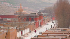 Street and golden dome of Gontang Pagoda at Labrang Monastery, China Stock Footage
