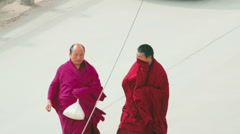 Two Tibetan Buddhist monks roam street of Labrang Monastery, China Stock Footage
