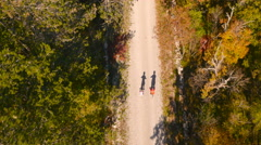 4K Aerial: Top View above Cycling Couple in Forest Road Stock Footage