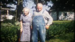 2773 - grandparents pose for photo at country home - vintage film home movie Stock Footage