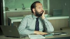 Bored, young businessman sitting by table in office Stock Footage
