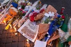ROME, ITALY - NOVEMBER 14, 2015: Flowers and lit candles in front of the Fren Stock Photos