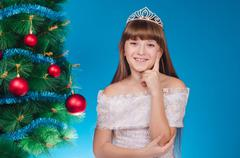 The girl in a dress with a diadem costs at a beautiful New Year tree smiles. - stock photo