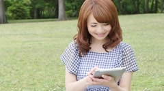 Young attractive Japanese woman with tablet in a city park Stock Footage
