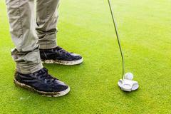Hitting a golf ball with a putter club - stock photo
