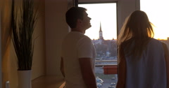 Man and woman looking at the city from balcony Stock Footage