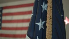 Sliding shot of US Flag in foreground with larger flag unfurled in background - stock footage