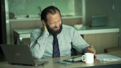 Young businessman having neck pain during work on laptop and tablet in office Stock Footage