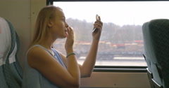 Young woman putting make-up in train Stock Footage
