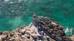 Cliff Jumping into Ocean. Aerial View Slow Motion. Young Man Jumps off Cliff  Stock Footage