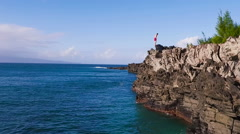 Stock Video Footage of Cliff Jumping into Ocean. Aerial View Slow Motion. Young Man Jumps off Cliff