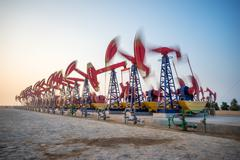 Working oil-rig in oilfield in clear sky Stock Photos