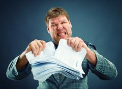 Stock Photo of Angry man tear out paper