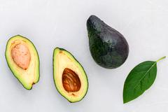 Alternative health care fresh  avocado and leaves on marble background. Stock Photos