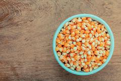 Grains of ripe corn in the bowl on teak wood background . - stock photo