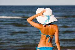 Sexy girl in big hat on the beach - stock photo