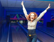 Excited girl in a bowling Stock Photos
