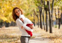 Young mother with sleeping child on hands in autumn park - stock photo
