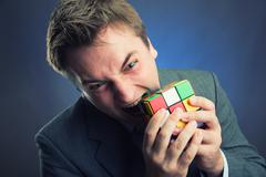 Businessman holding rubik cube in his hands Stock Photos