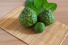 Bergamot and the leaf on makisu mat on wood texture Stock Photos