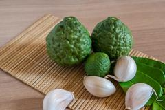 bergamot and garlic on makisu mat on wood texture - stock photo