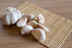 Garlic cloves on makisu mat on wood texture Stock Photos