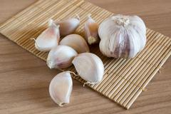 Garlic cloves on makisu mat on wood texture Stock Photos