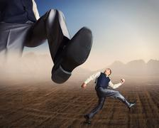 Businessman runs from a big foot - stock photo