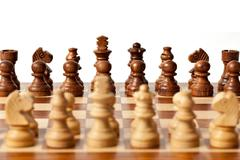 Wooden chess pieces on chessboard. Selective focus, shallow depth of field - stock photo