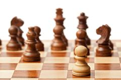 One pawn agains all - wooden chess pieces on chessboard. Selective focus, sha Stock Photos