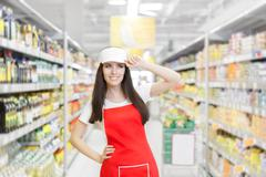 Smiling Supermarket Employee Standing Among Shelves Stock Photos
