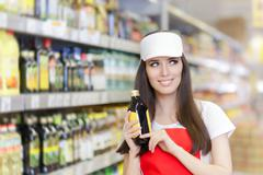 Smiling Supermarket Employee Holding a Product - stock photo