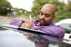 young man writing notes in a textbook - stock photo