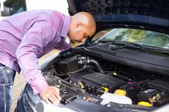 man looking at his car engine - stock photo