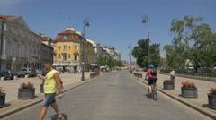 Two men riding bikes on Krakowskie Przedmiescie street on a sunny day in Warsaw Stock Footage