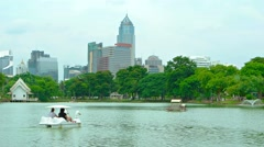 Tourists pedaling a rented boat on a manmade lake in Lumphini Park Stock Footage