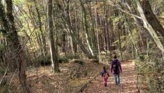 Child with her mother walking on forest road Stock Footage