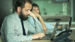 Bored busiesspeople with laptop sitting by table in office Stock Footage