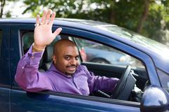 man waving goodbye from his car - stock photo