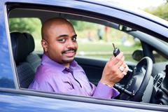 Driver with a steering wheel spinner showing his car key Stock Photos