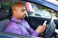 Man stopped at a carpark to check his phone messages - stock photo