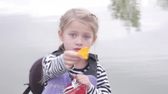 Cute little girl eating chips on a canoe Stock Footage