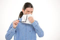 Young handsome man sneezing and using handkerchief - stock photo