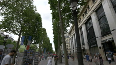 Traffic on Avenue des Champs-Elysees, next to Louis Pion store in Paris Stock Footage
