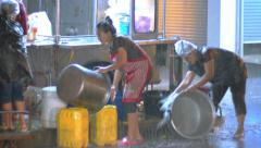 Street vendors scrubbing pots in the hevy rain in downtown Bangkok. - stock footage