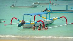 Local children swimming in ocean and climbing on outriggers of boat Stock Footage