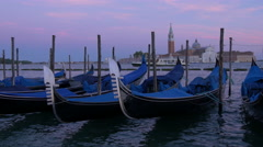 Gondolas moored to mooring posts at dusk in Venice Stock Footage