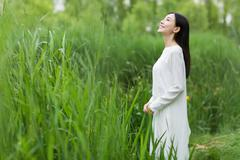 woman in whiter dress summer amidst reed - stock photo