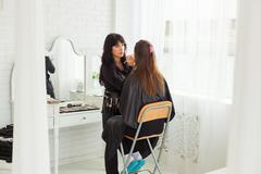 Make-up master doing visage indoors - stock photo