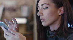 Young female designer is testing user interface on a smartphone and computer Arkistovideo